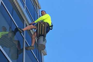 Man cleaning windows on hoist